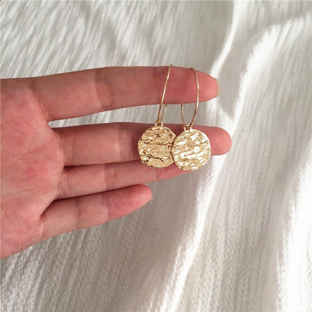 boucles d'oreilles dorées cercles pleins texturés reflets eau